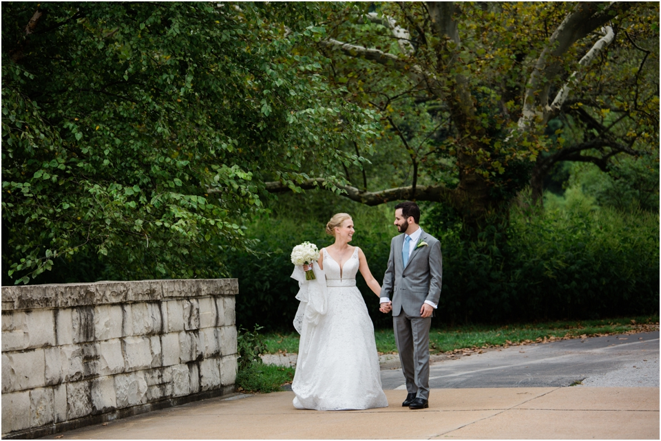 Bride and groom holding hands, walking across a bridge in Forest Park