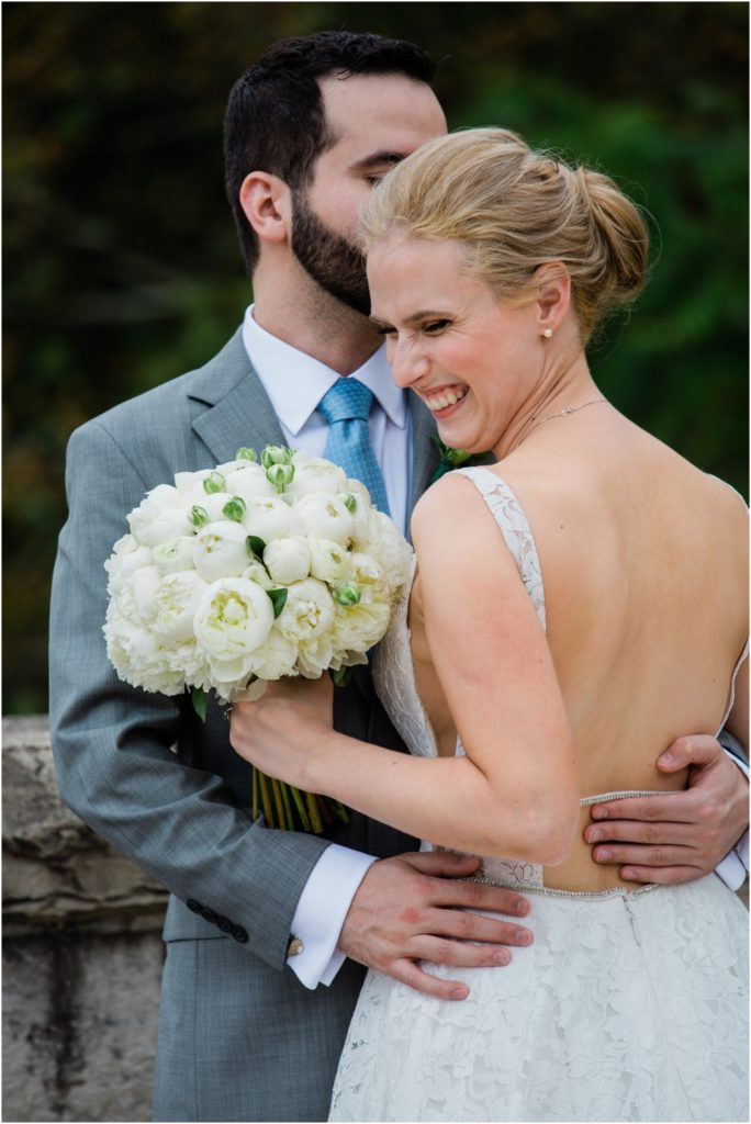 Bride laughing as groom kisses her on her head