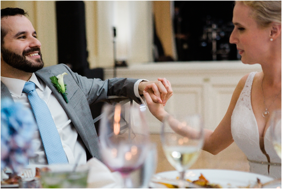 Bride and groom holding hands during maid of honor toast