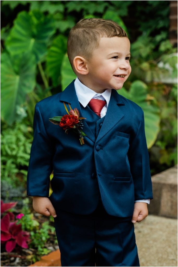 Ring barer in navy blue suit with burgundy tie and red flower boutineer