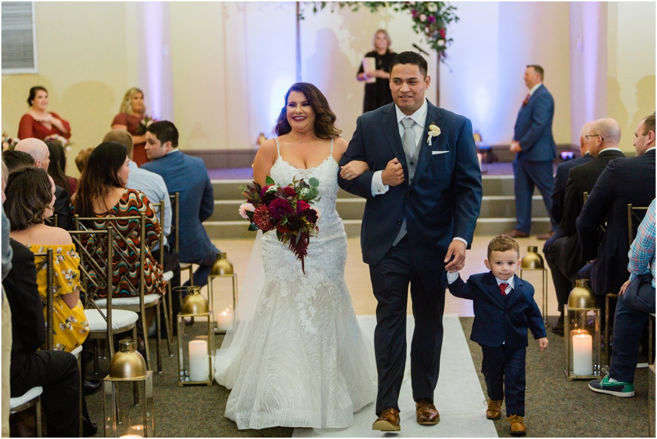 bride and groom walking up the aisle with their son after wedding ceremony