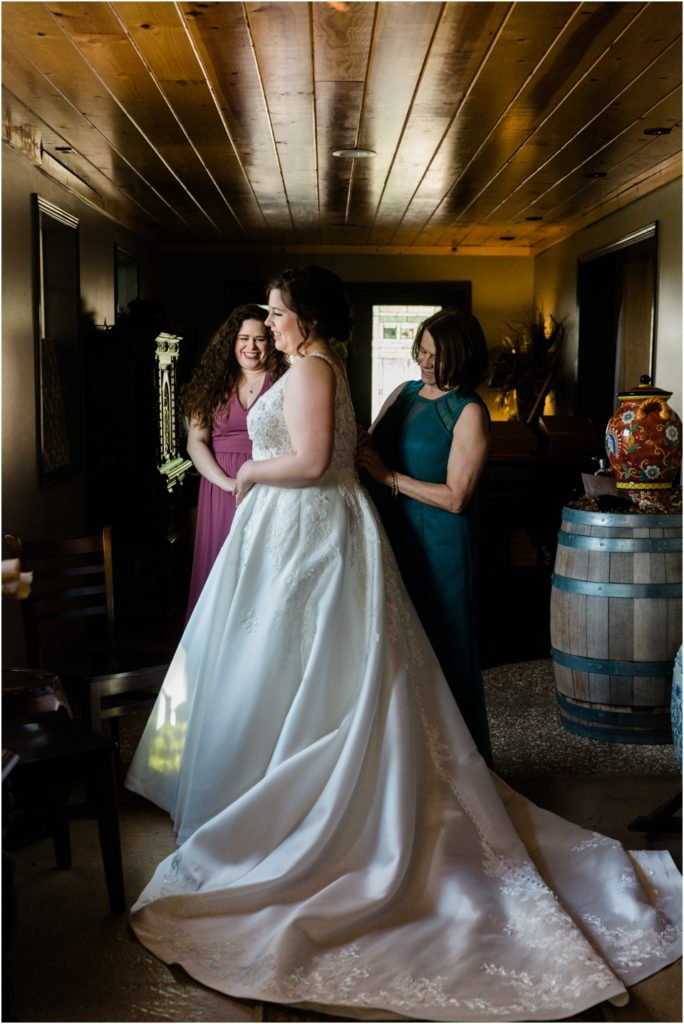 Bride getting ready while her mom zips her dress