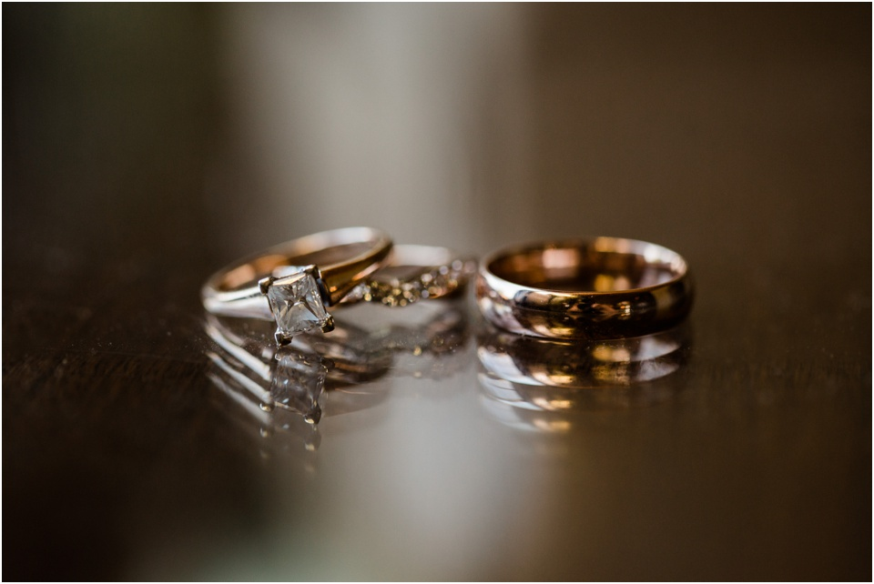 Wedding and engagement rings reflected in glass table top