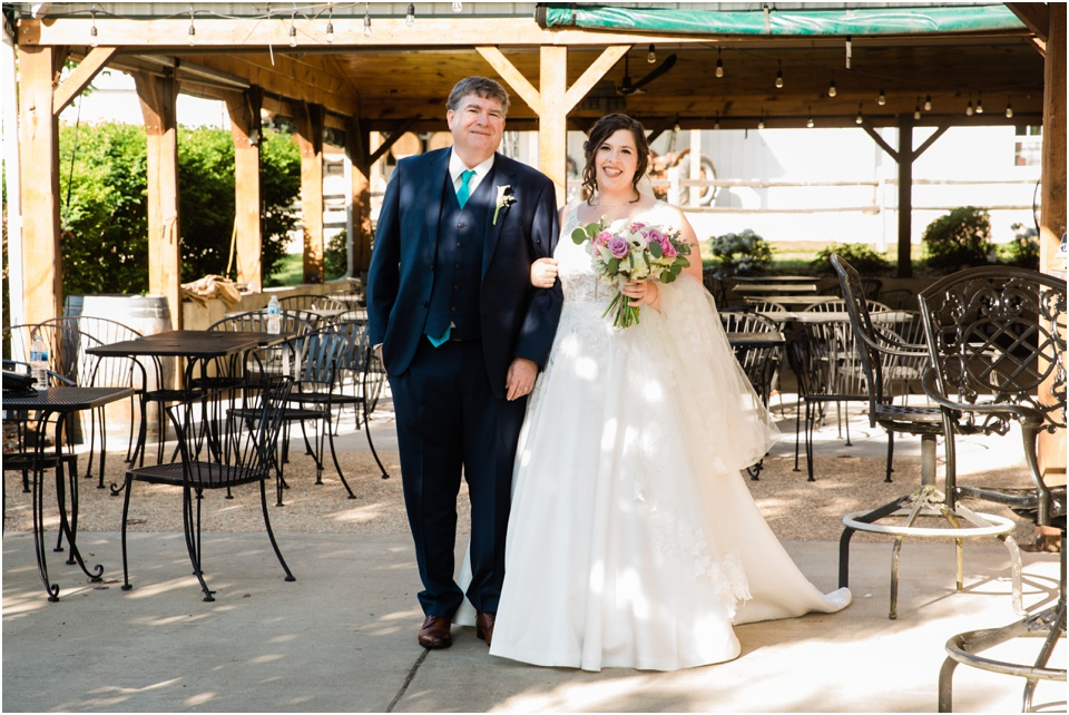 Father walks the bride across the patio