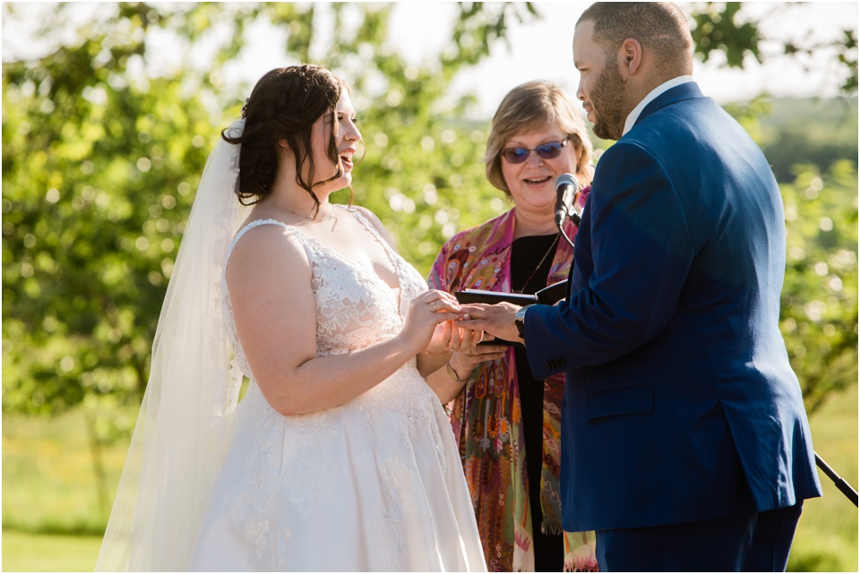 Bride says I do as she puts the ring on the groom's finger
