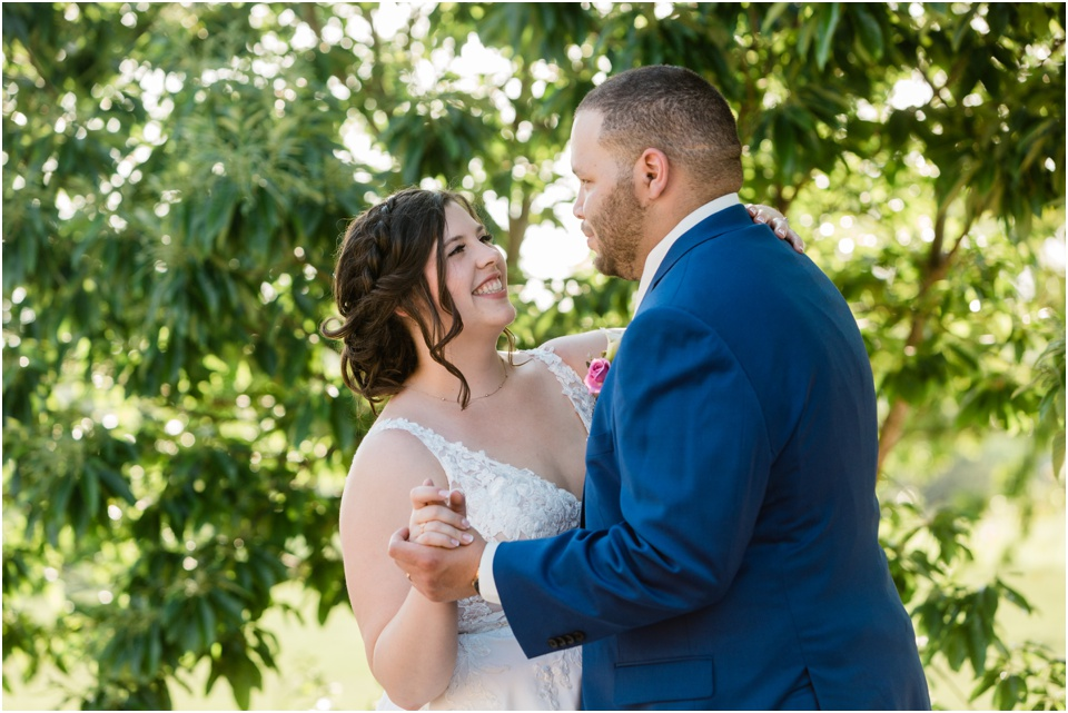 Bride and groom laugh during first dance on the patio at Belmont Vineyards Winery.