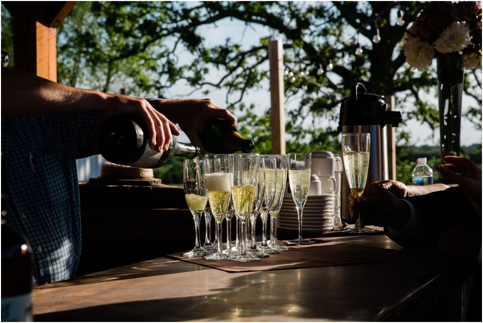 Bartender pours glasses of champagne at dusk at Belmont