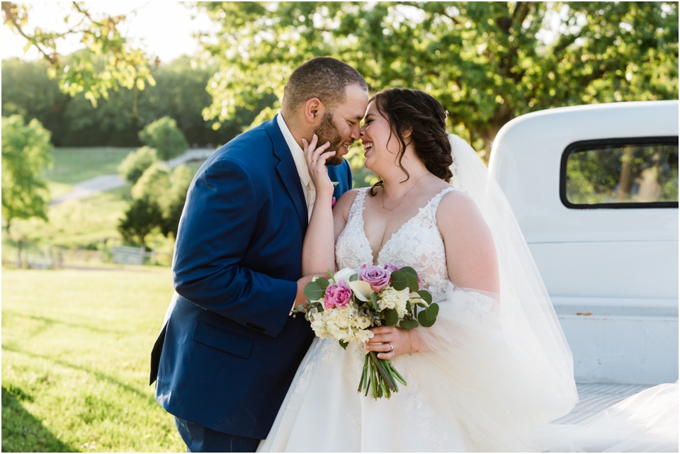 Bride and groom laugh into a kiss on the bed of a white 50's pickup truck
