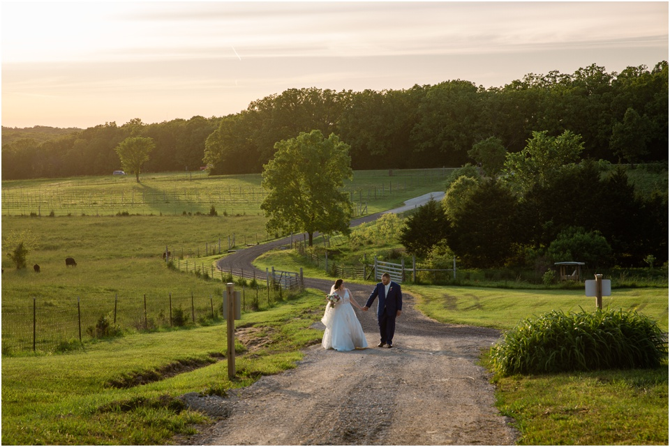 Bride and groom walk up the dirt road at Sunset Belmont Vineyards Winery in Leasburg, Missouri
