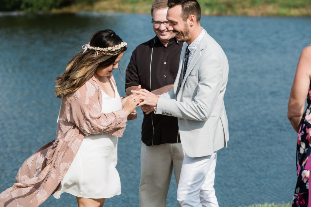 The exchanging of rings in an intimate wedding ceremony in front of the lake.