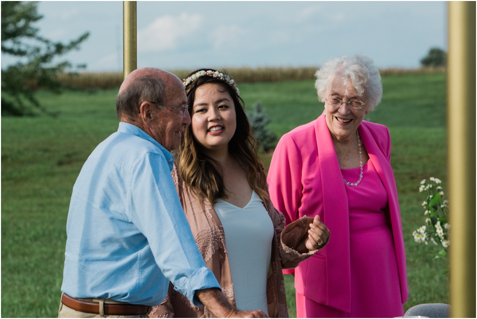 Bride shows grandparents to their seats for intimate wedding reception.
