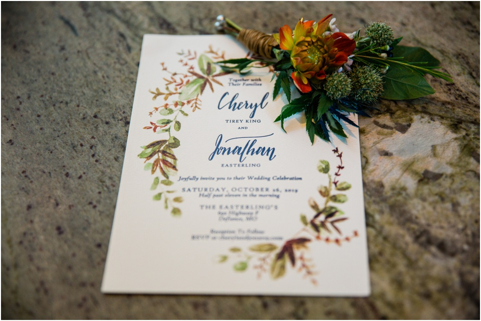 Fall wedding invitation on marble counter top with boutonniere