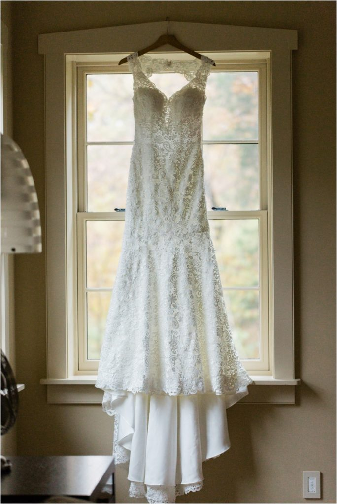 Antique, white, lace wedding dress hanging back lit by the window
