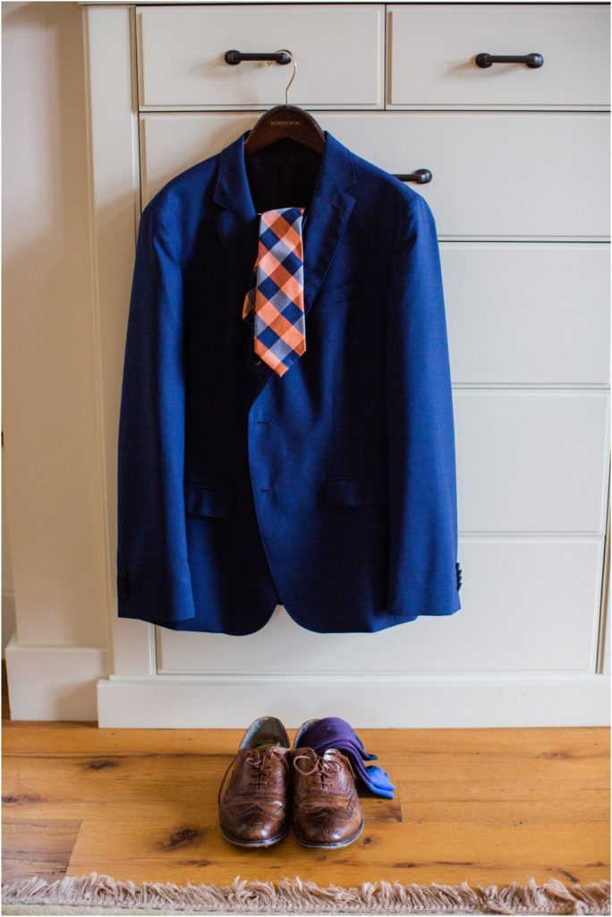 Groom's navy blue suit jacket hanging with orange and blue checked tie