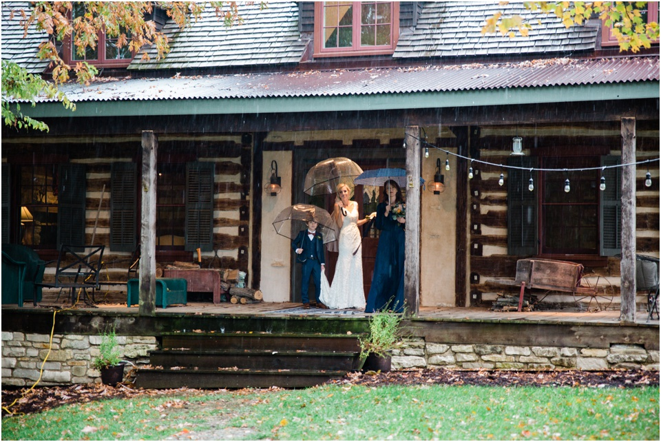 Bride stands on cover porch of log cabin under a clear umbrella waiting to walk up the aisle