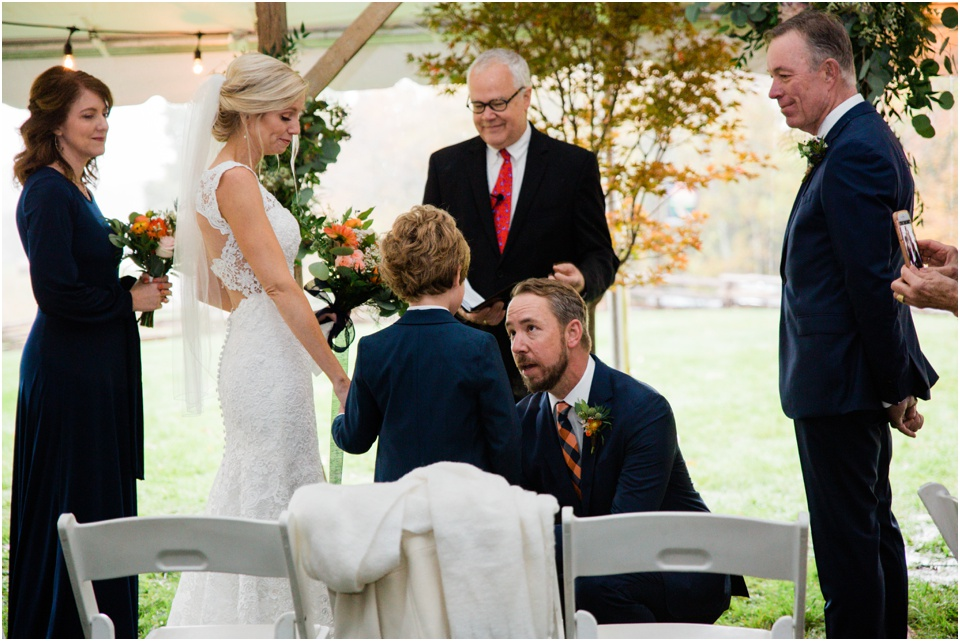Groom stoops down to talk to his new step son at the alter
