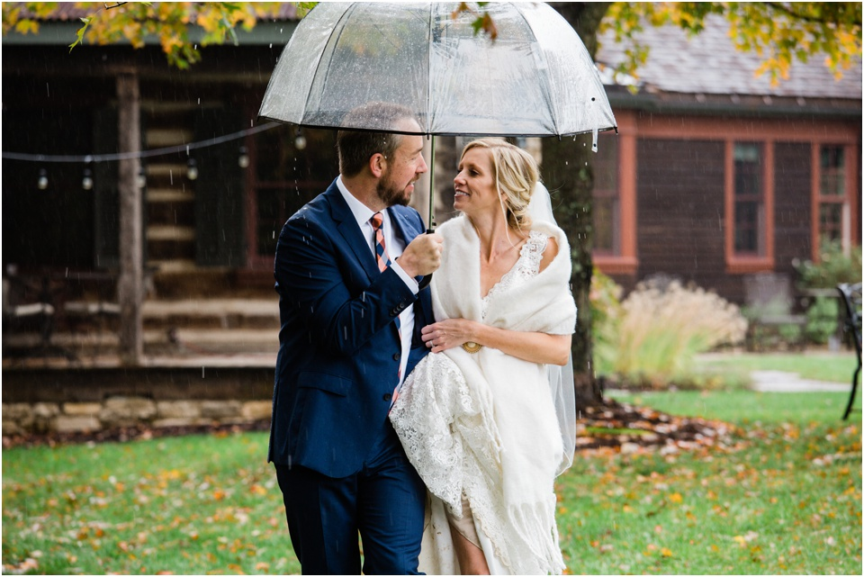 Groom holds bride close while holding a clear umbrella over them as they walk trough the rain