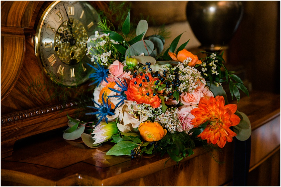 Orange, red, blue, pink and green bridal bouquet lies on wooden table next to antique clock