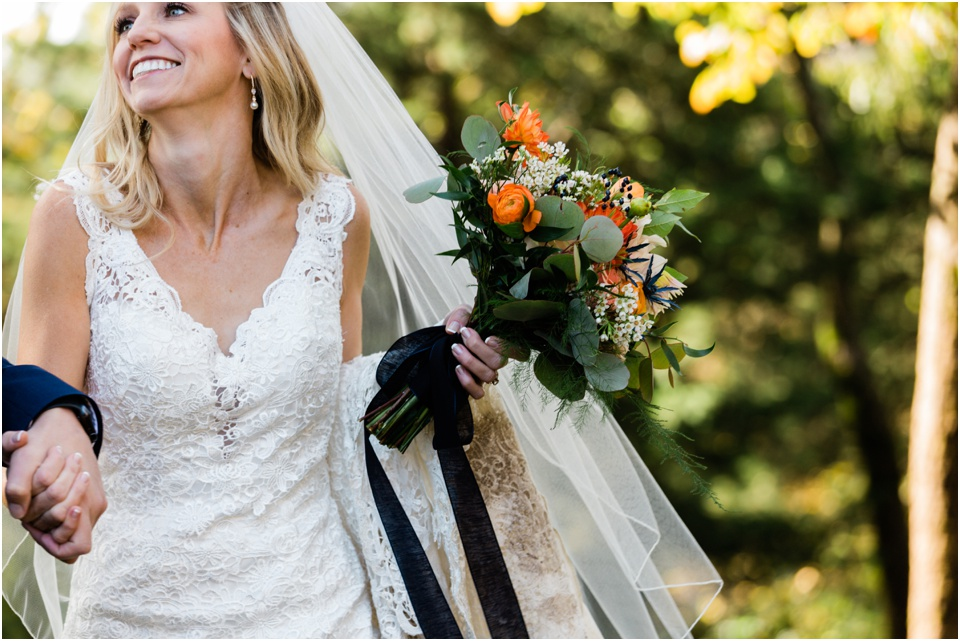 Bride smiling at groom off camera while navy blue ribbons trail her vibrant fall bouqet