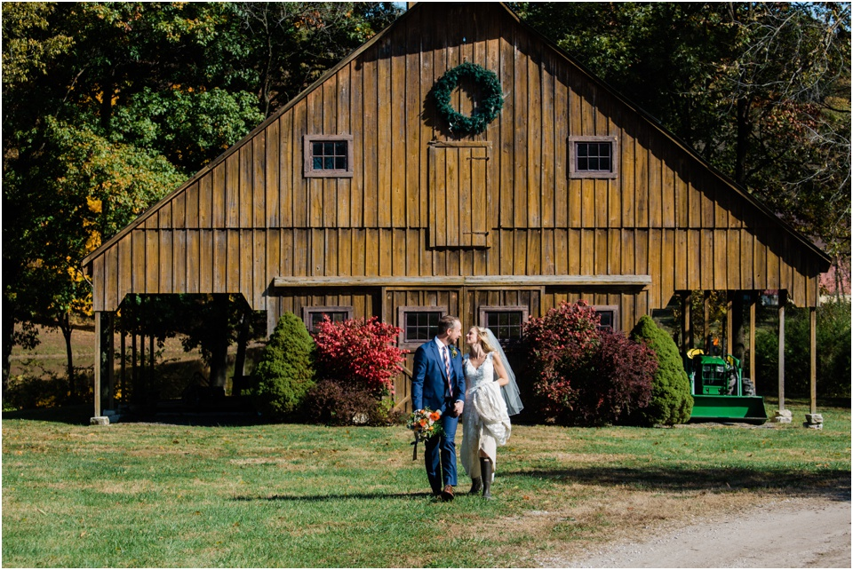Bride and groom walking together with old, weathered barn behind them