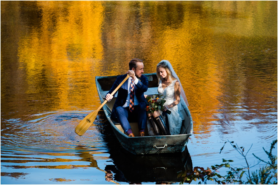 Groom rows boat into shore with sun shining on bride and fall leaves reflect in the lake around them