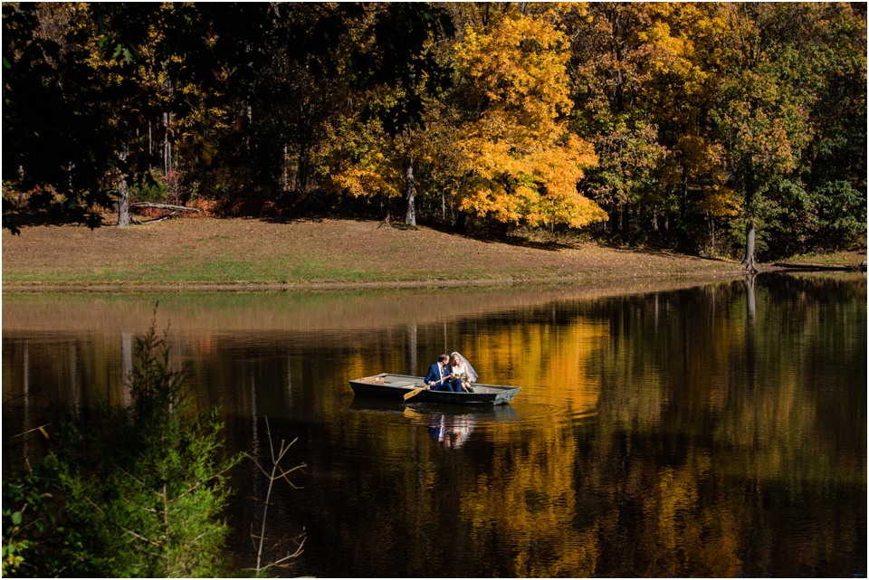 Bride and groom in a rowboat with the yellow leaves of fall reflecting in the water all around them